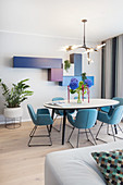 Oval dining table and blue chairs in open-plan interior with modular, wall-mounted cupboards