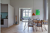 Dining table with slender lines and chairs in open-plan interior with kitchen in custom-made cube