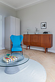 Round coffee table, turquoise armchair and retro sideboard in living room