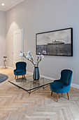 Two easy chairs and glass table below artwork on wall