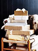 Verpackte Weihnachtsgeschenke auf Holzstuhl mit Tierfell