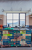 Kitchen counter covered in vintage-style wallpaper below window