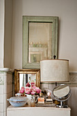 A selection of mirrors and perfumes on cabinet in shabby chic tiled bathroom