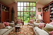 Wohnzimmer in Rosatönen mit Couch, antiken Polsterstühlen und Bücherwänden
