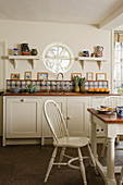 White furnishings and round window above counter in simple, rustic kitchen