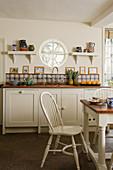 Ländlich rustikale Küche mit weißen Küchenmöbeln und Rundfenster über Küchenzeile