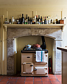 Cream AGA cooker in fireplace of country-house kitchen