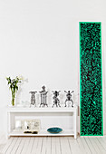 Delicate paper sculptures on white shelves and panel of black-and-green paper art