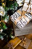 Verpackte Weihnachtsgeschenke unter und neben dem Tannenbaum
