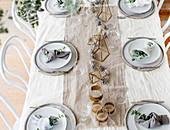 Weihnachtlich gedeckter Tisch mit Tischläufer, Zapfen und geometrischen Dekoobjekten