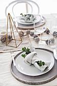 Weihnachtlich gedeckter Tisch mit Serviettendeko, Zapfen und geometrischem Dekoobjekt