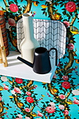 Vase, small watering can and tray on white wall shelf in front of floral wallpaper