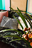 Cushions on sofa with botanical pattern, orchid in the foreground