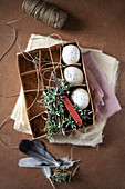 Speckled eggs, chickweed and twine in egg box