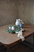 Osternest mit besprenkelten Eier und Kännchen auf Tisch