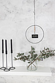 DIY wall decoration: metal ring with motto above vase of eucalyptus branches and black candles