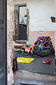 Colourful rug draped over rocking chair in Mediterranean house
