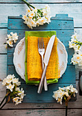 Spring table setting - narcissus flower, Fork and knife on Easter table
