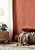 Pillows, blankets and teaware on rugs in front of brick-red wall, houseplant in front of window