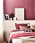 Double bed in front of the ledge with decorative objects in the bedroom, dark red wall and matching accessories