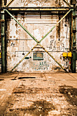 Abandoned factory floor with peeling paint on walls