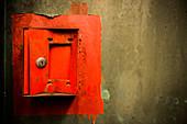 Eingedrückter roter Metallkasten an der Wand
