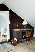 Old desk against rustic wooden wall in attic