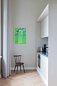 Chair in simple fitted kitchen in period apartment with green poster on wall