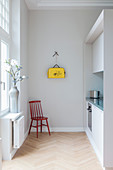 Chair in simple fitted kitchen in period apartment with yellow bag on wall