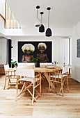 Round solid wood table with director's chairs in an open living room