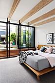 Double bed in elegant bedroom with window front