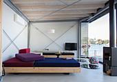 Modern houseboat: custom sofas, log burner and TV in living area