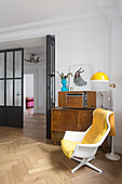 Yellow blanket on designer chair in front of retro sideboard and radio