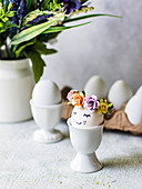 Easter eggs with flower decorations in eggcups