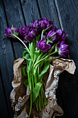 Lila Tulpen 'Purple Peony' mit Packpapier auf Holzuntergrund