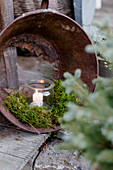 Candle in mason jar and moss arranged in metal bucket with rusted-through bottom