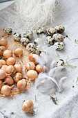 Pearl onions, quail eggs, feathers and decorative sisal straw on coarse fabric