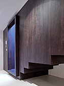 Staircase boxed in with dark wood