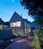Blick vom Garten auf beleuchtetes Haus bei Abendstimmung