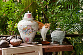 A cat stands between two vases on tabletop with old gourds and palms in the background