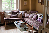 L-shaped, dusky pink velvet sofa with various scatter cushions
