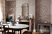 Wohnraum mit Esstisch und Kamin vor altrosafarbener Wandtapete mit Blütenmotiv