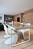 Oak panelling, glass dining table and designer chairs in modern interior