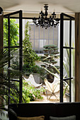 View through open window into courtyard with designer Butterfly chairs