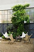 Sitzgruppe mit Designerstühlen im Innenhof mit Kiesboden
