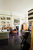 Französischer Ledersessel, Antikmöbel und Kunstwerke an der Wand im Wohnzimmer mit dunklem Dielenboden