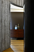 View of wooden sideboard through doorway in curved concrete wall