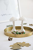 Autumnal arrangement of mushroom ornaments and acorns made from marbles on golden tray on table