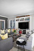 Grey sofa set, metal trunk used as coffee table and TV on shelves in living room