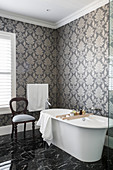 Free-standing bathtub in bathroom with patterned wallpaper and marble floor tiles